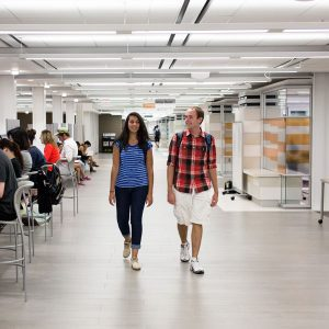 Two students walking down the long hallway of the Learning Commons of the first floor of the UI Main Library.
