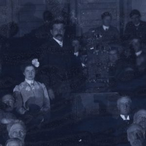 Brinton in a crowd near the projector for a film